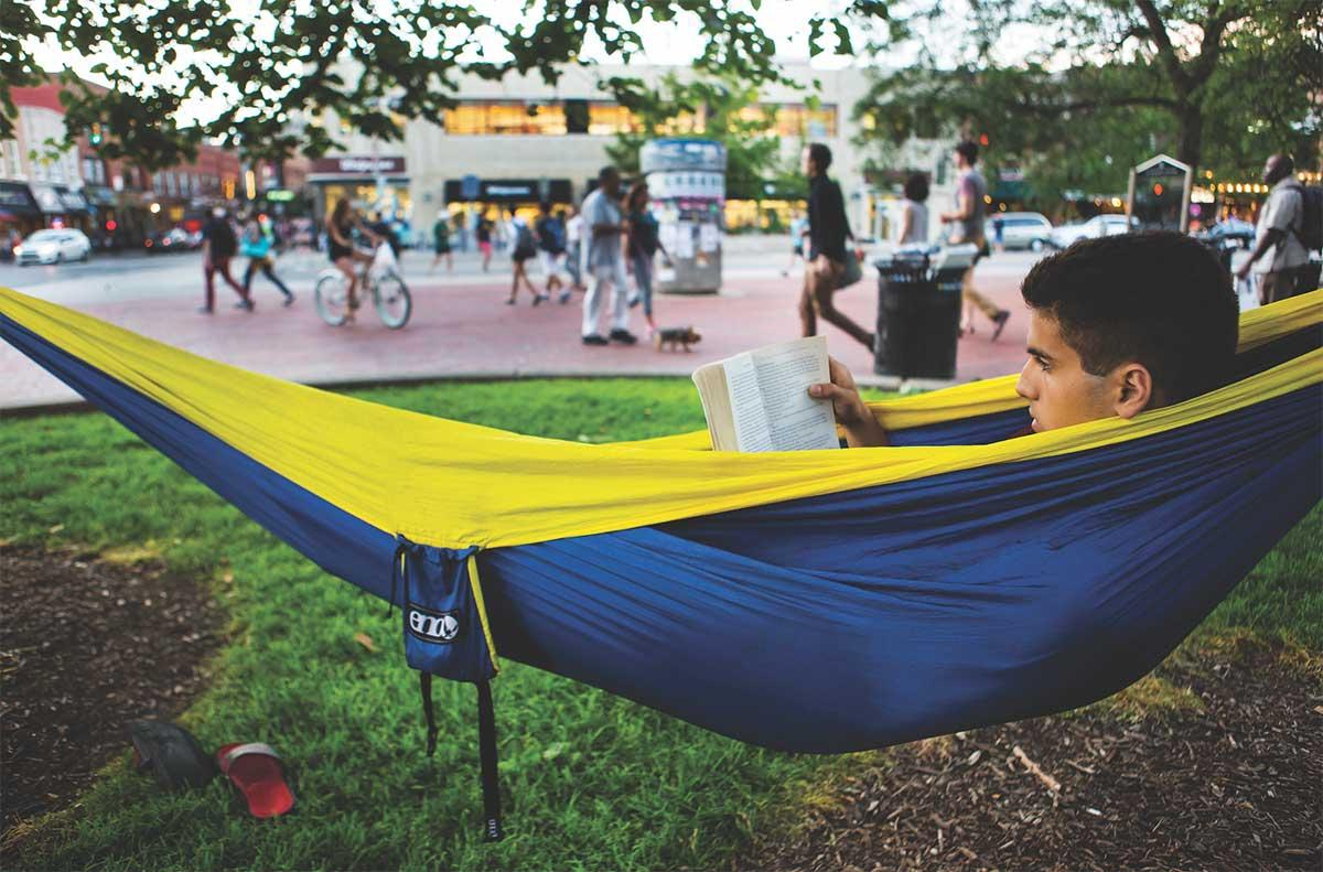 student reading a book in a hammock