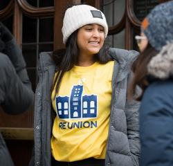 Woman student wearing a winter coat and hat and a University of Michigan t-shirt