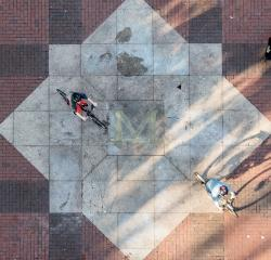 Two students biking across the block M on the Diag