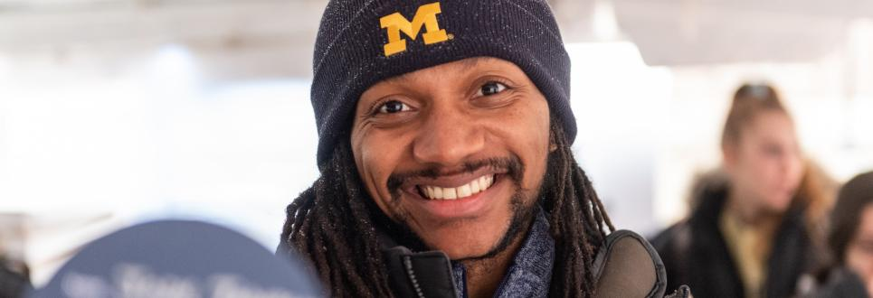 A student smiling while wearing a University of Michigan hat