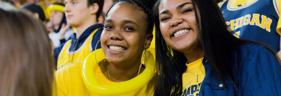 Two women students smiling while at a sporting event, wearing all maize and blue