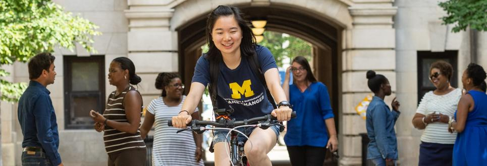 Student biking through the West Hall arch