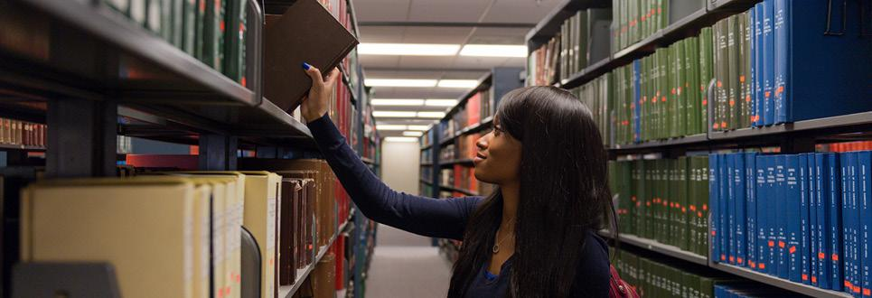 A student puts a book back on a shelf in the library