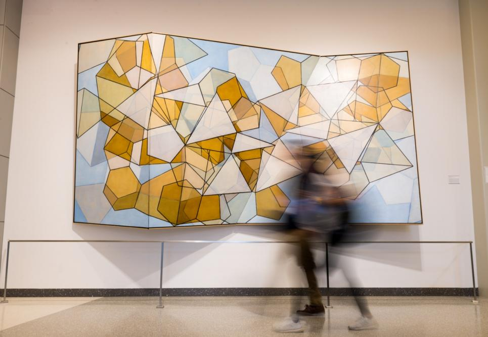 A student walking very fast past a large painting of geometric shapes