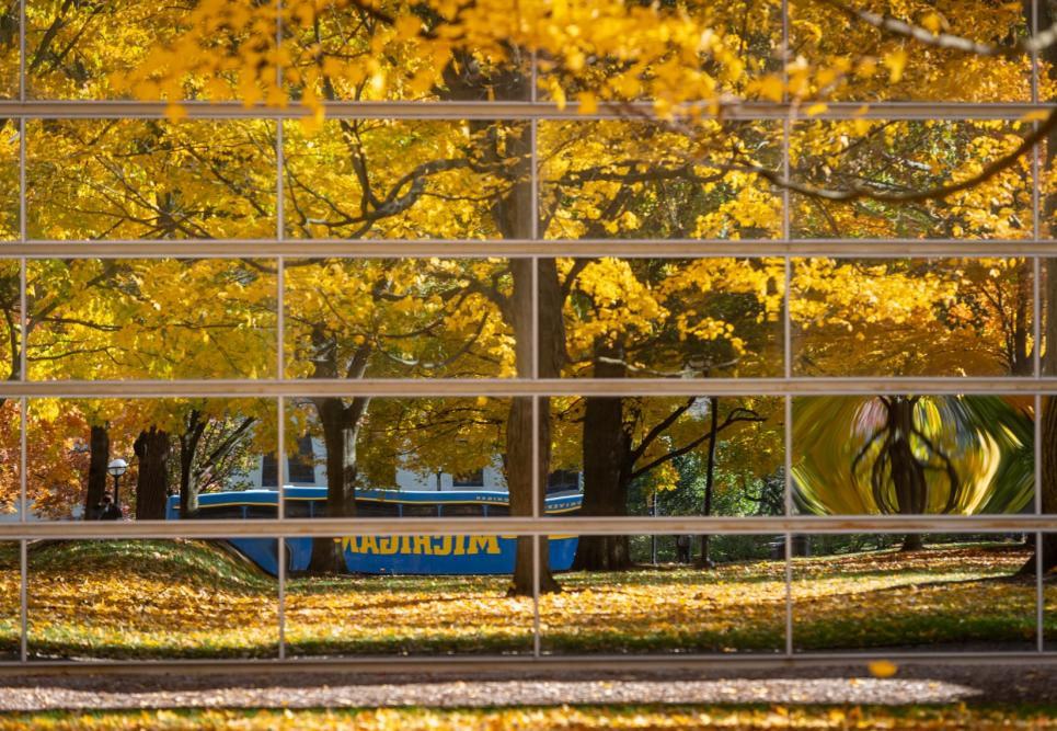 A bus reflected by windows in fall